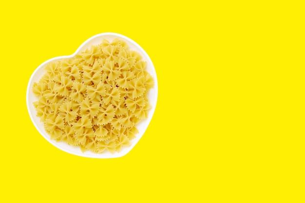 Piatto bianco a forma di cuore riempito con papillon di pasta cruda su sfondo giallo, maccheroni a farfalla.