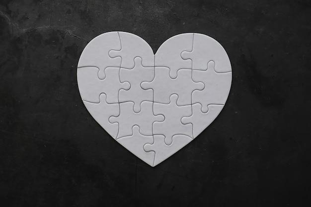 Puzzle a forma di cuore bianco. affari di cuore. amore indiviso. cuore spezzato. la chiave del cuore. cuore chiuso su una serratura. concetto di amore.