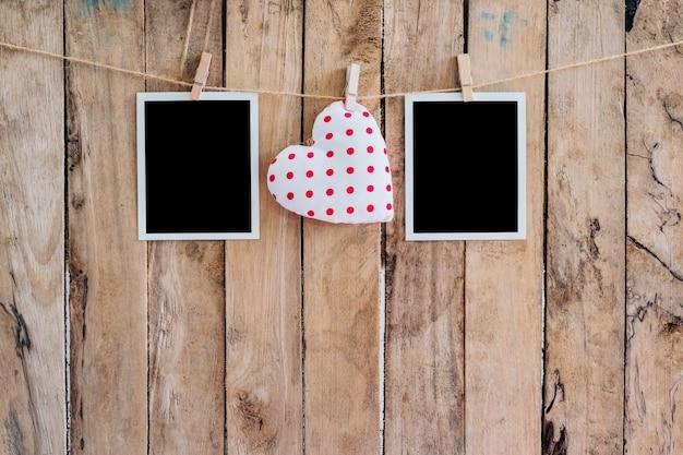 Cuore bianco e due cornice fotografica appesa sulla corda clothesline con sfondo in legno.