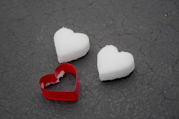 Cuori bianchi fatti di neve che si scioglie con un tagliabiscotti di colore rosso