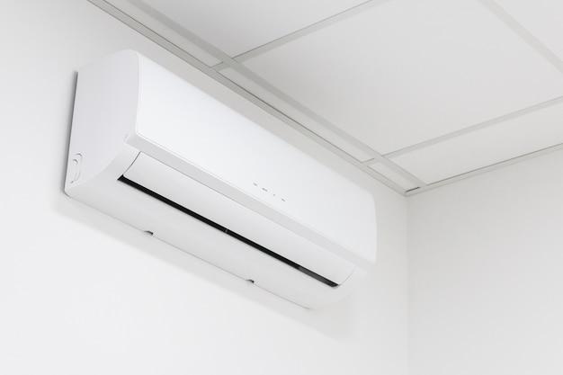 Condizionatore d'aria bianco di riscaldamento e raffreddamento sulla parete bianca in ufficio o in casa.