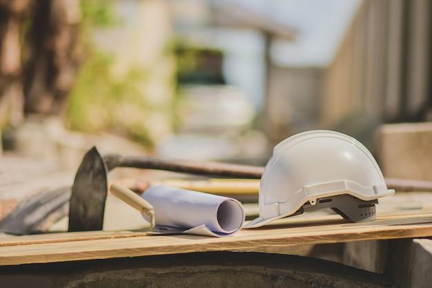 Cappello duro del casco bianco sul pavimento di legno nel sito di costrizione