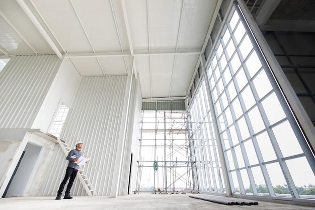 L'ingegnere maschio del casco bianco con stampa blu sta controllando la struttura dell'edificio in costruzione