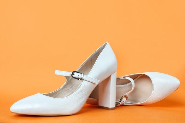Le scarpe bianche delle donne del tacco alto su una parete arancio. vista laterale, da vicino.