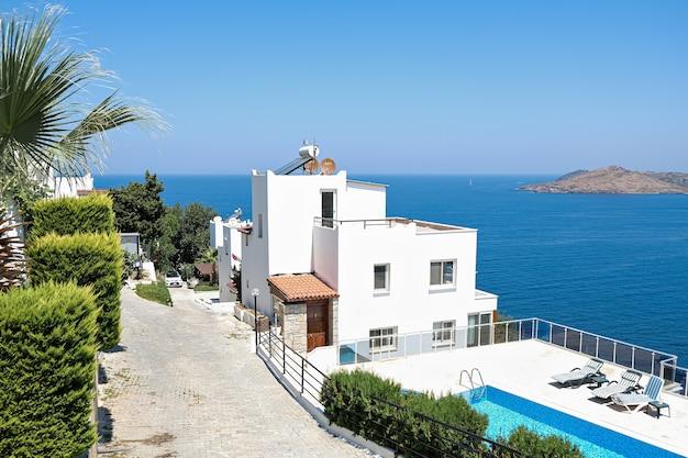 Case bianche ville per vacanze in resort con vista mare e piscina e palme.