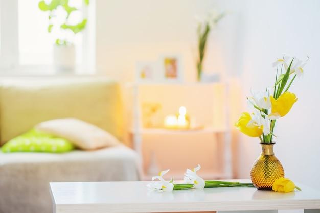 Interno domestico bianco con fiori e decorazioni primaverili