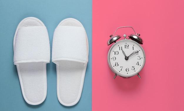 Pantofole a pelo bianche dell'hotel e sveglia colorate