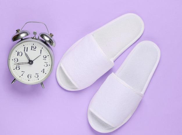Pantofole e sveglia di sonno dell'hotel bianche sulla porpora