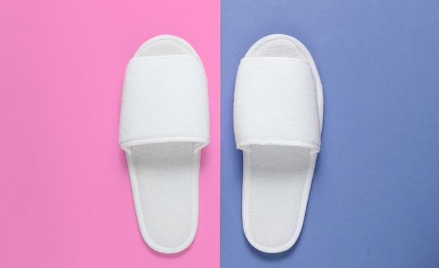 Pantofole a pelo bianche dell'hotel su colorate.