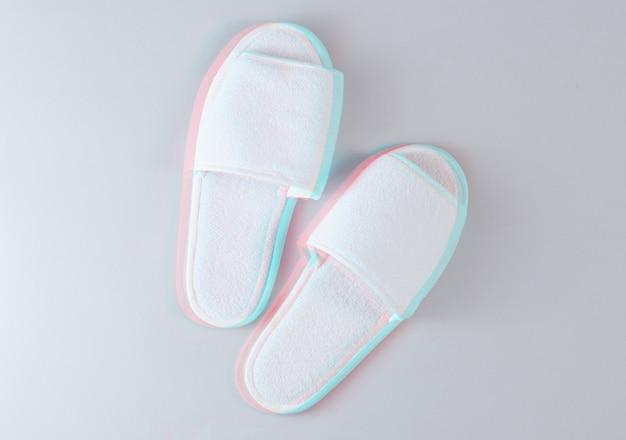 Pantofole da letto bianche dell'hotel su un grigio