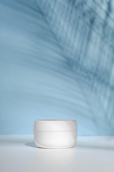 Un barattolo bianco di crema su un supporto, su un tavolo bianco con foglie di palma tropicali e la loro ombra.