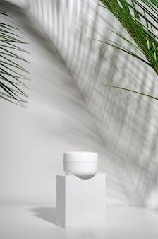 Vaso bianco di crema su un supporto su un muro bianco con foglie di palma tropicali e la loro ombra.