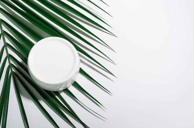 Barattolo bianco di crema su una tavola bianca con le foglie di palma tropicali.