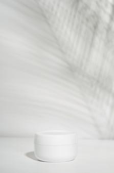 Barattolo bianco di crema su un bianco con l'ombra tropicale delle foglie di palma