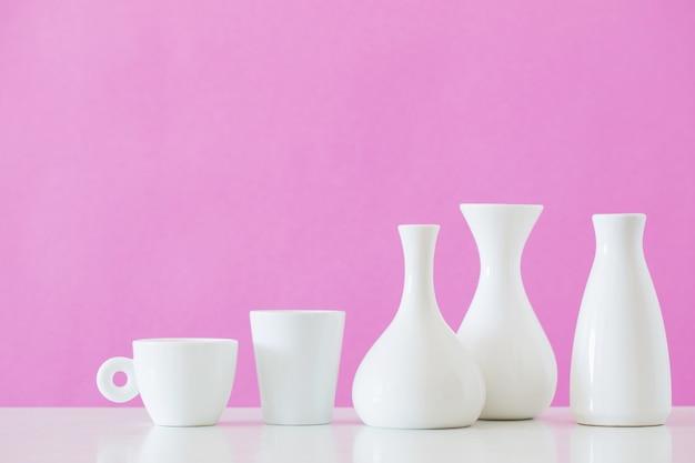 Vasetti bianchi sul muro rosa