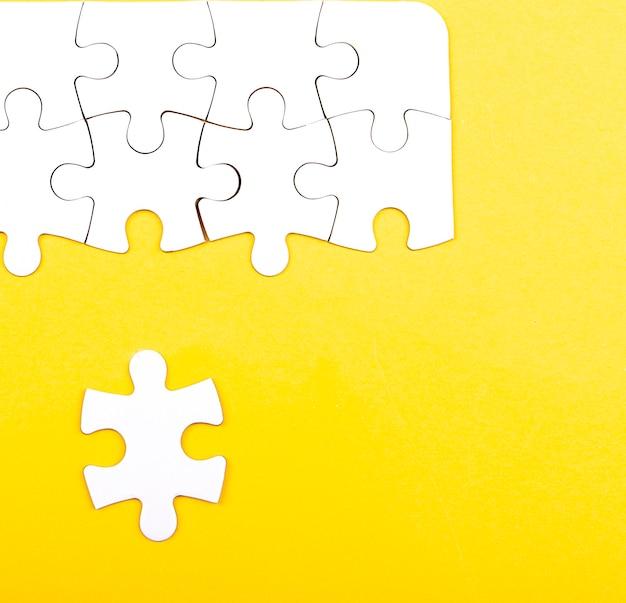 Puzzle bianco isolato su uno sfondo giallo