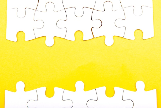 Pezzi di un puzzle bianco isolati su uno sfondo giallo