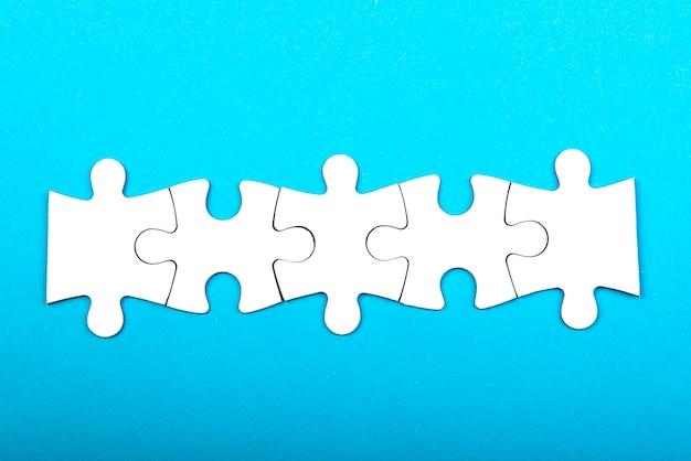 Riga di pezzi di puzzle bianco