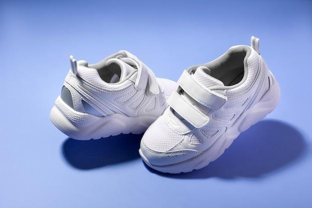 Sneakers galleggianti per bambini bianche con chiusure in velcro l'una di fronte all'altra isolate su sfondo viola con...