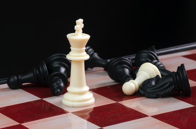 Il re bianco in primo piano tra il pedone sulla scacchiera