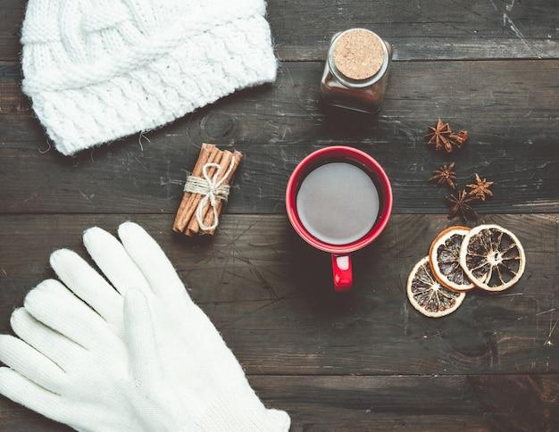 Guanti bianchi lavorati a maglia e tazza rossa con un drink su un tavolo in legno marrone, vista dall'alto