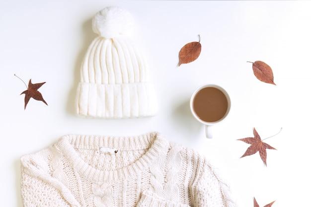 Maglione bianco lavorato a maglia, cappello di lana, una tazza di caffè e foglie di acero essiccate su un blackground bianco, piatto disteso