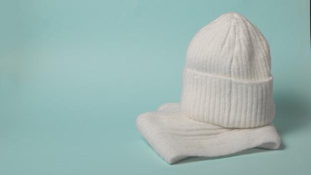 Guanti e cappello da donna lavorati a maglia bianchi. accessori invernali alla moda.