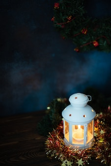 Lanterna bianca con candela accesa e rami di abete