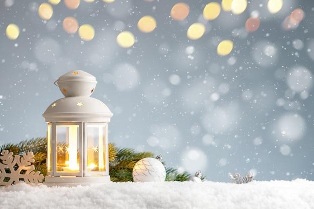 Lanterna bianca con decorazioni natalizie in un cumulo di neve sull'azzurro