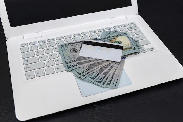 Computer portatile bianco con dollari e carta di credito isolati