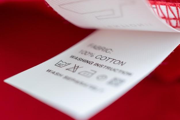 Etichetta bianca per il lavaggio delle istruzioni per la cura del bucato su una camicia di cotone rossa