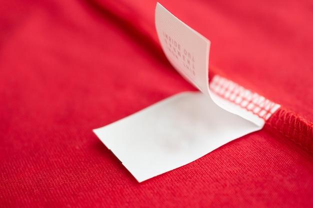 Etichetta di vestiti di istruzioni di lavaggio per la cura della biancheria bianca sulla camicia di cotone rossa