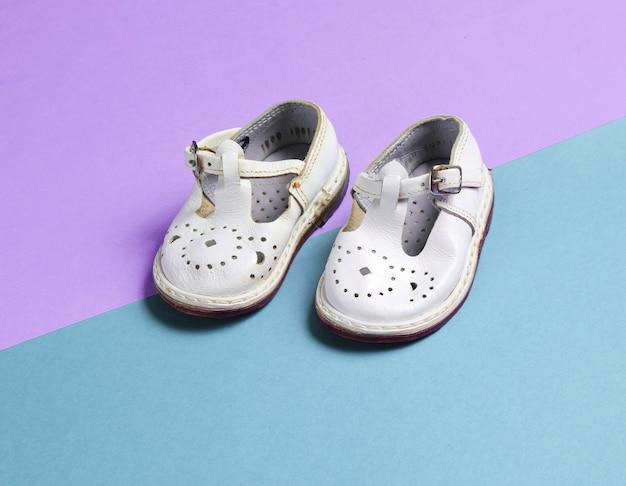 Sandali da bambino in pelle bianca su colori pastello.
