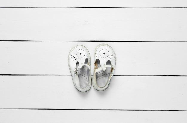 Sandali per bambini in pelle bianca su legno bianco.