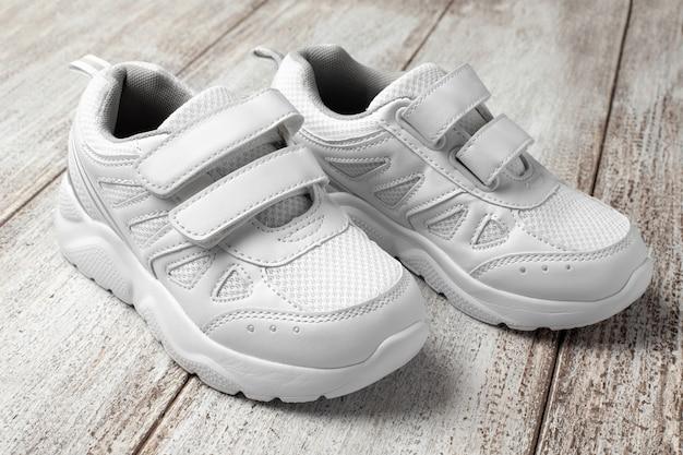 Sneakers in pelle bianca su sfondo chiaro un paio di sneakers sportive per bambini alla moda con un...