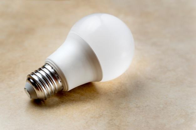 Lampada led bianca con filo normale su sfondo marrone chiaro con spazio copia a destra