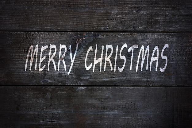 Lettering bianco buon natale su fondo di legno nero