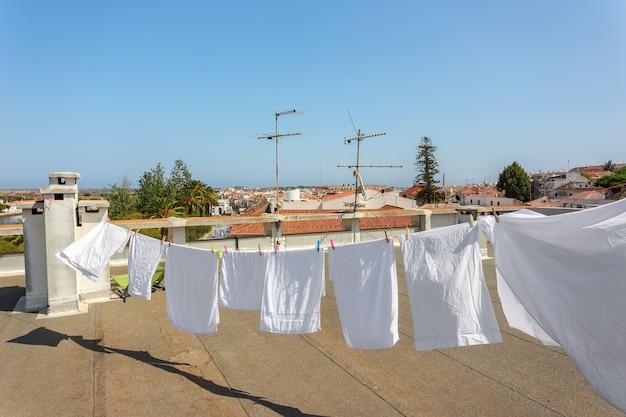 Biancheria bianca, appesa ad asciugare sul tetto del balcone.