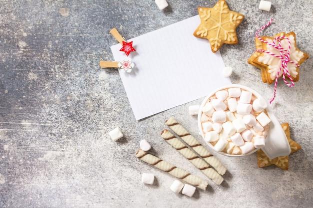 Lista bianca e tazza di cioccolata calda con marshmallow e cottura natalizia su un piano di lavoro in pietra