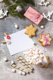 Lista bianca e tazza di cioccolata calda con marshmallow e cottura natalizia vista dall'alto piatta