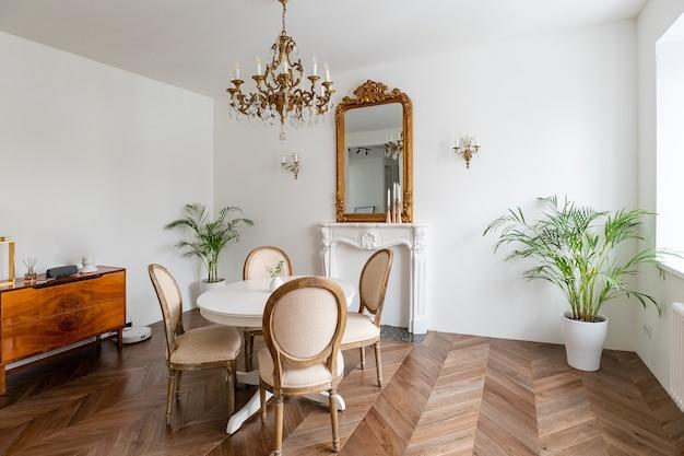 Soggiorno bianco con arredamento classico, specchio, camino, tavolo da pranzo.