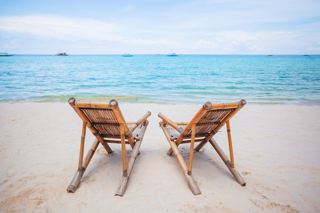 Sedie a sdraio bianche su una bellissima spiaggia tropicale alle maldive