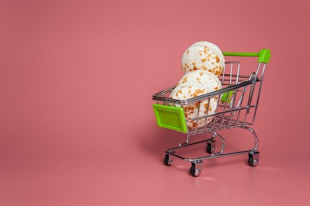 Macarons bianchi in un carretto su sfondo rosa