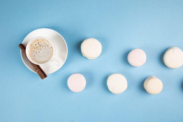 Macarons bianchi e caffè con cannella su una superficie blu