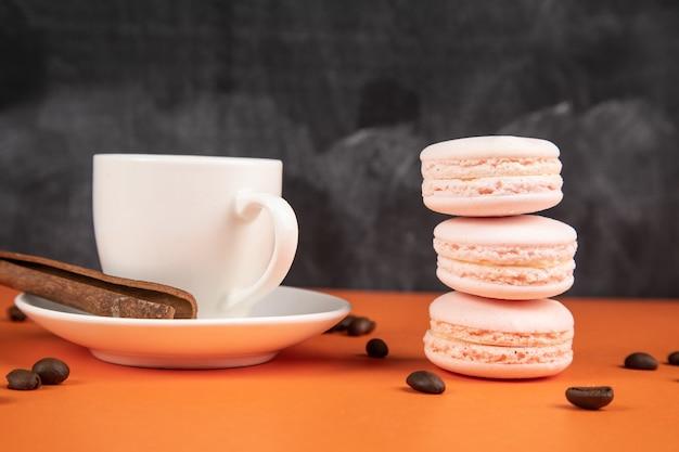Macarons bianchi e caffè con cannella su una superficie arancione. semi di caffè