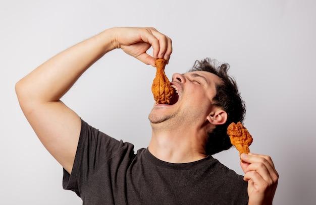 Uomo bianco in maglietta nera con cosce di pollo sul muro bianco