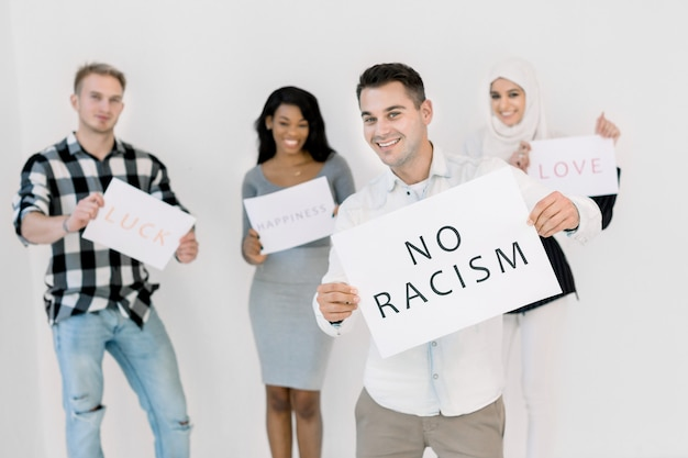 Un uomo bianco in abbigliamento casual detiene un poster con il testo no razzismo nelle sue mani, in piedi su sfondo bianco