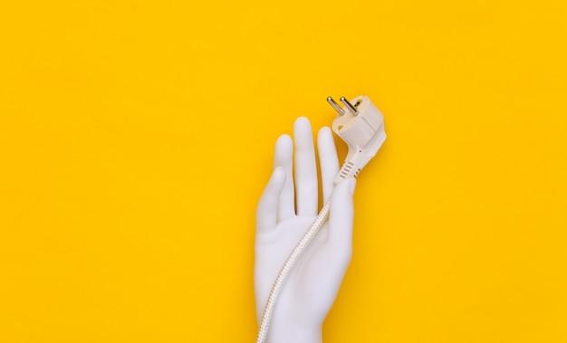 La mano bianca del manichino tiene la spina elettrica con il cavo su fondo giallo.