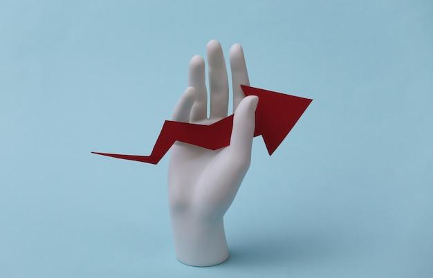 Una mano di manichino bianco tiene una freccia di crescita rivolta verso l'alto su uno sfondo blu. affari, concetto di economia