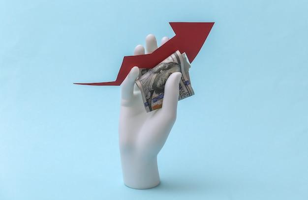 La mano bianca del manichino tiene la freccia di crescita rivolta verso l'alto con banconote in dollari su sfondo blu. affari, concetto di economia